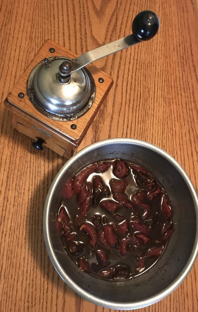 Venison jerky pieces in marinade in stainless steel bowl on a table next to an antique coffee grinder