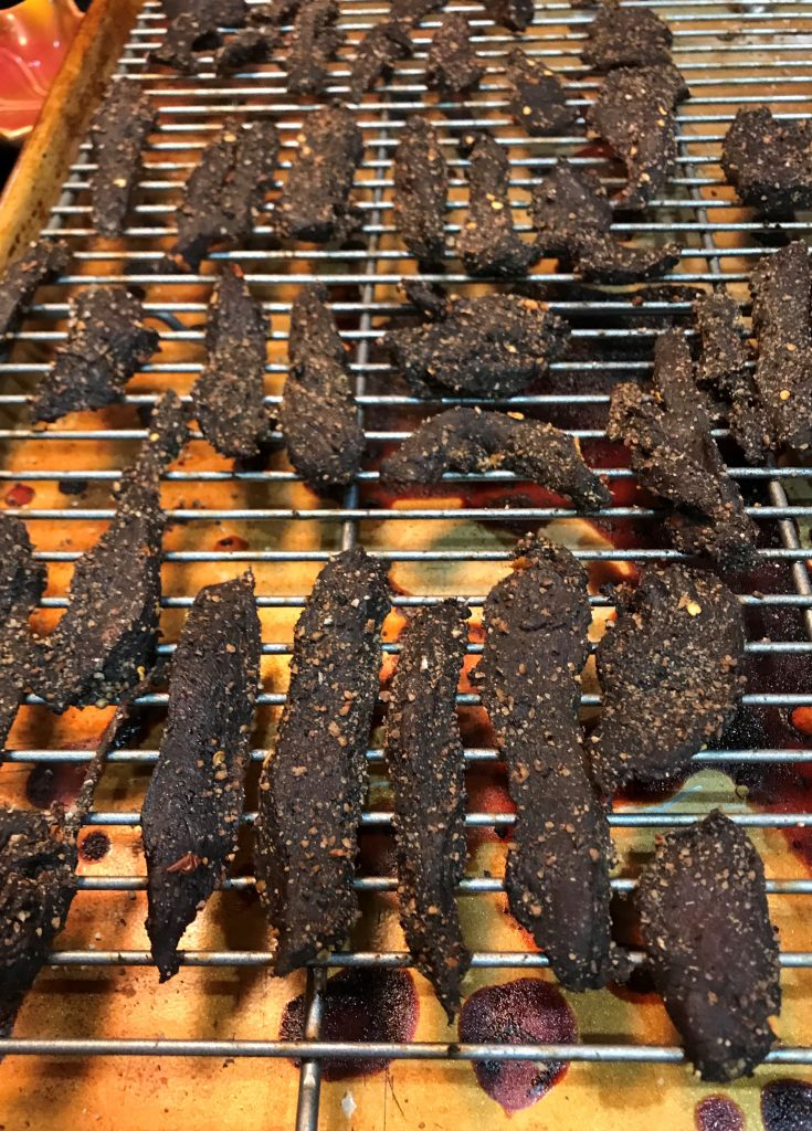 venison jerky on cooling rack on pan