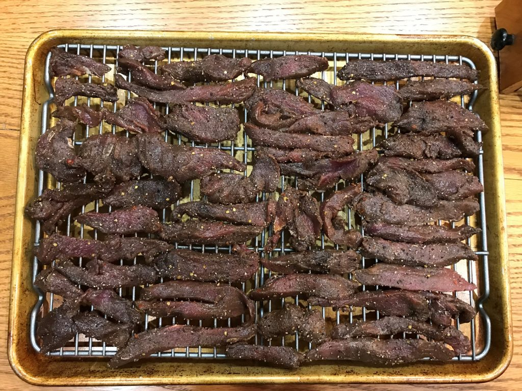 raw venison jerky pieces on cooling rack on pan