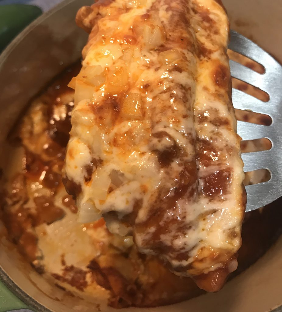 Cheese enchiladas on metal spatula